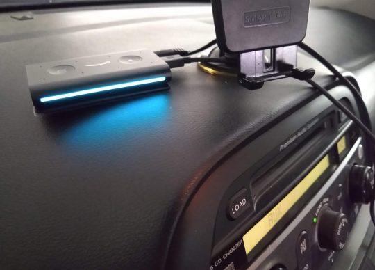 amazon auto echo next to a phone mount on a vehicle dash