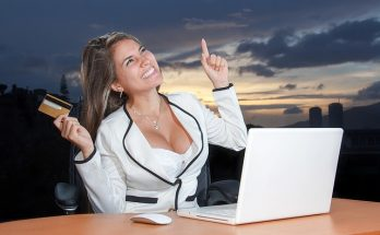 business woman with credit card and laptop, smiling and pointing up